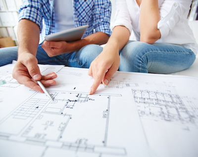 Hands of young couple during discussion of plan of flat